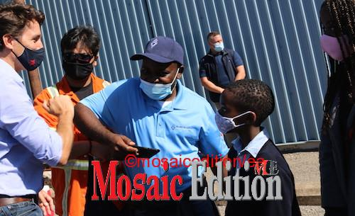 Justin Trudeau bumps elbow in pandemic greeting with a worker at Valbruna ASW INC. The worker was at the event with his children. Pandemic greeting. Photo Mosaic Edition Edward Akinwunmi
