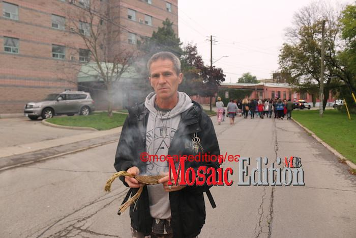Indigenous member of the community performs traditional cleansing as the procession went by. Photo Mosaic Edition Edward Akinwunmi.